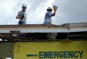 Helping to cover the roof of the emergency room to keep patients dry during constant rainstorms.